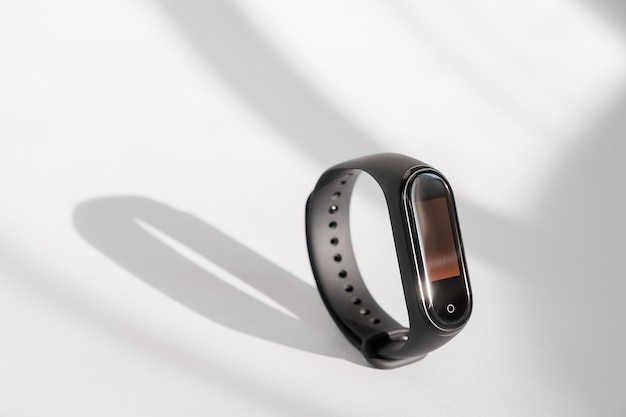 Slimme die geschiktheidsdrijver op witte ochtend lichte achtergrond wordt geïsoleerd. sport armband. fitness band run tracker. zwart fitnesshorloge.