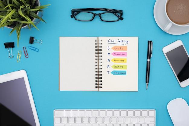 Slimme doelstelling met kantoorbenodigdheden over een blauw bureau
