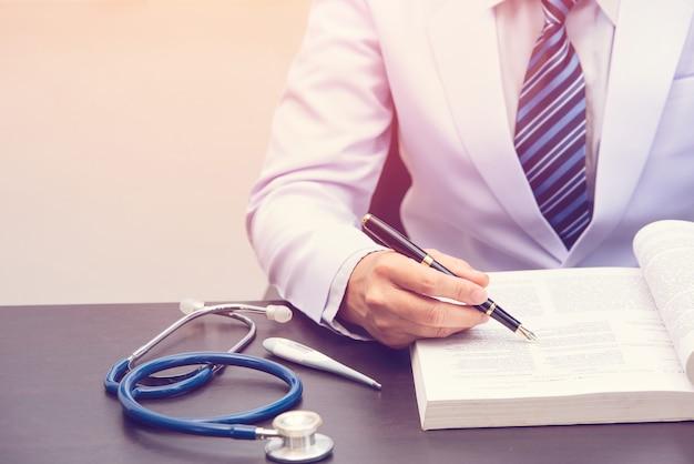 Slimme dokter situeert en leest boek arts die zwarte pen vasthoudt en naar het leerboek wijst