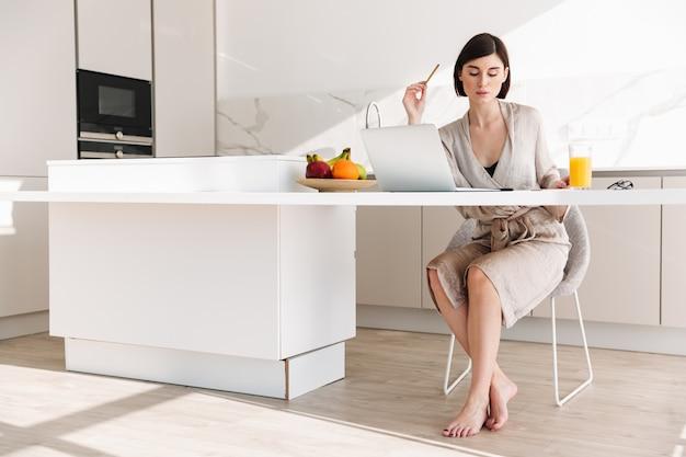 Slimme donkerbruine vrouw die badjaszitting bij lijst in vlakte dragen, en aan laptop werken terwijl het hebben van ontbijt
