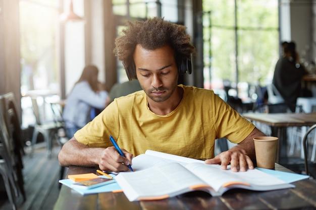 Slimme, donkere student die iets uit een boek schrijft en naar het audioboek in zijn koptelefoon luistert terwijl hij in de cafetaria zit tijdens zijn pauze, afhaalkoffie drinkt en hard werkt