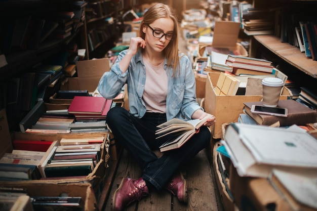 Slimme en slimme student zit op de vloer met haar benen gekruist en leest een boek heel voorzichtig. ze zoekt daar wat informatie. jonge vrouw ziet er serieus en geconcentreerd uit.