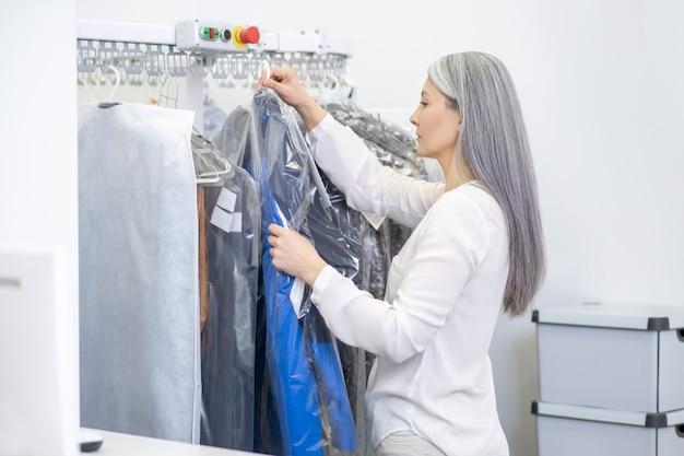 Slimme ernstige vrouw vrouw met lang grijs haar permanent zijwaarts opknoping schoon verpakte kleren op rek