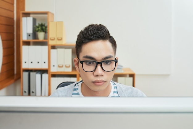 Slimme etnische man aan het werk op computer