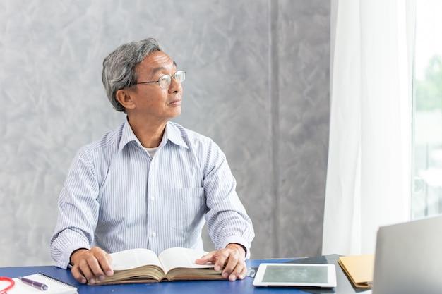 Slimme gezonde zakelijke oude man zit in kantoor, aziatische ouderling denkt uit de ramen te kijken tijdens het lezen van een boek.