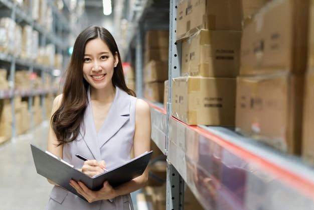 Slimme glimlachende aziatische vrouw die in opslagpakhuis werkt.