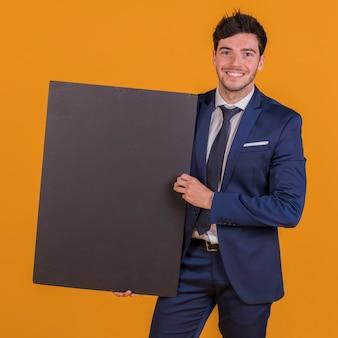 Slimme glimlachende jonge mens die zwart aanplakbiljet houden in hand tegen een oranje achtergrond