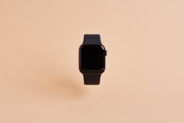 Slimme horloge apparaat geïsoleerd op lichtoranje muur