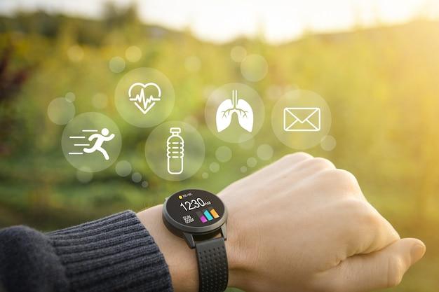 Slimme horloge, fitnesstracker bij de hand in de buitenlucht op een wazig groen