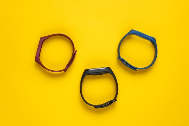 Slimme horloge met verwisselbare armbanden op gele achtergrond. fitnesstracker. moderne gadgets