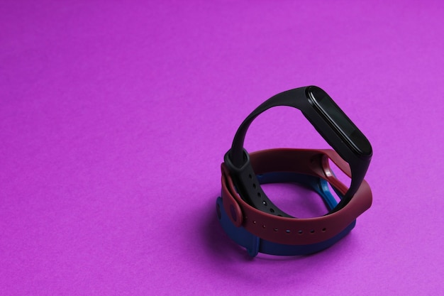 Slimme horloge met verwisselbare armbanden op paarse achtergrond. fitnesstracker. moderne gadgets
