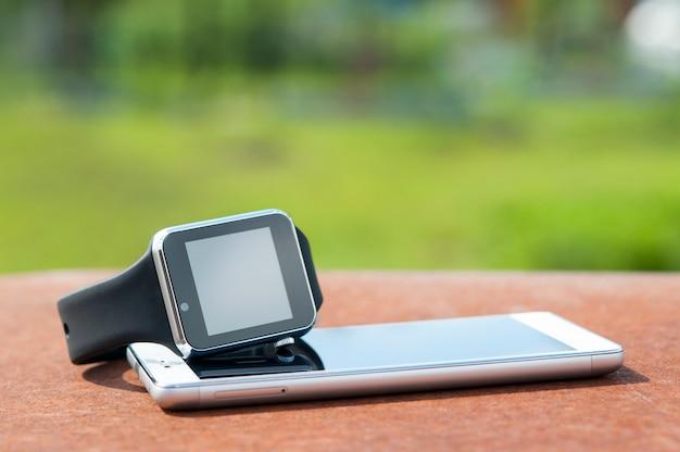 Slimme horloges staan aan de telefoon, op de achtergrond van de natuur.