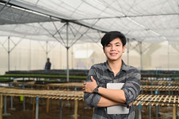 Slimme jonge aziatische boer die een digitale tablet vasthoudt terwijl hij in een kas staat gevuld met biologische groenten.