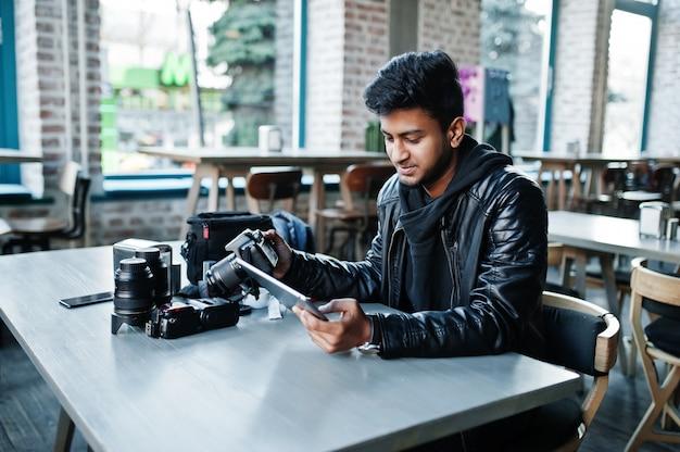 Slimme jonge aziatische mensenfotograaf die met tablet werkt tijdens het zitten bij koffie