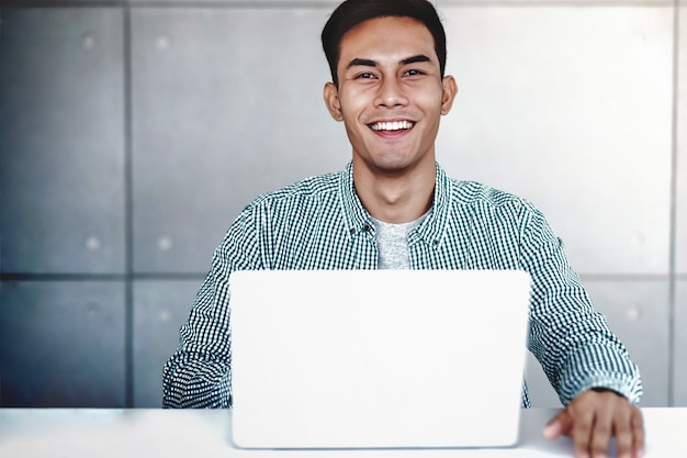 Slimme jonge aziatische zakenman die aan computerlaptop in bureau werkt. lachend en kijkend naar camera