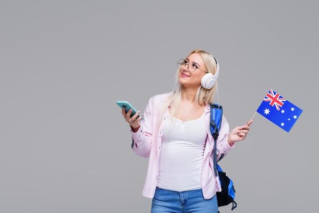 Slimme jonge blonde vrouw in hoofdtelefoons tevreden met het leren van taal tijdens online cursussen met smartphone, glimlachende vrouwelijke student huiswerk taak, informatie zoeken via mobiele telefoon