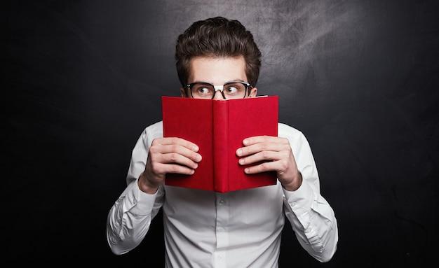 Slimme jonge mannelijke nerd student in glazen gezicht verbergen achter open rode boek en nieuwsgierig kijken tijdens het studeren