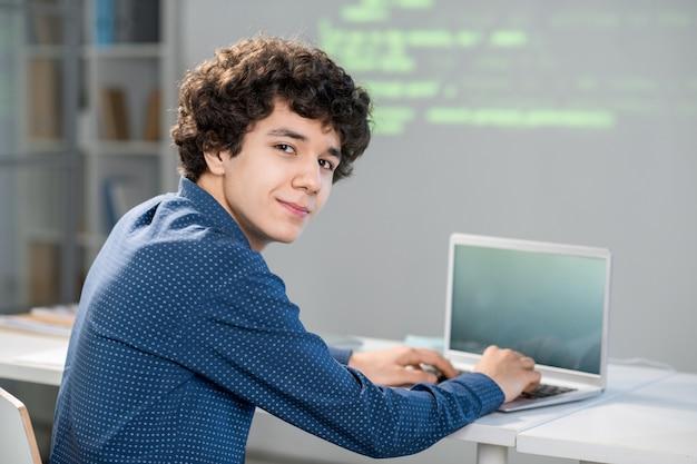 Slimme jonge student met krullend haar die naar je kijkt terwijl je aan een bureau zit en met technische gegevens werkt of een presentatie voorbereidt