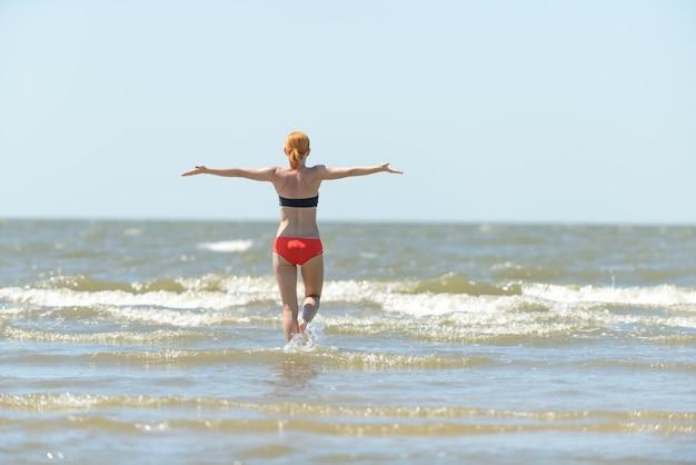 Slimme jonge vrouw die in zee golven loopt