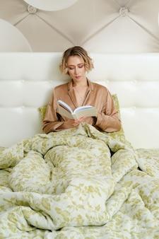 Slimme jonge vrouw zit in bed onder de deken met een boek in handen