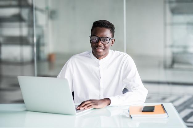 Slimme jonge zakenman die de computer in bureau bekijkt