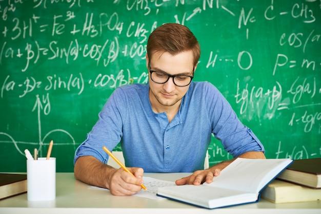 Slimme jongen die zeer geconcentreerd zijn huiswerk