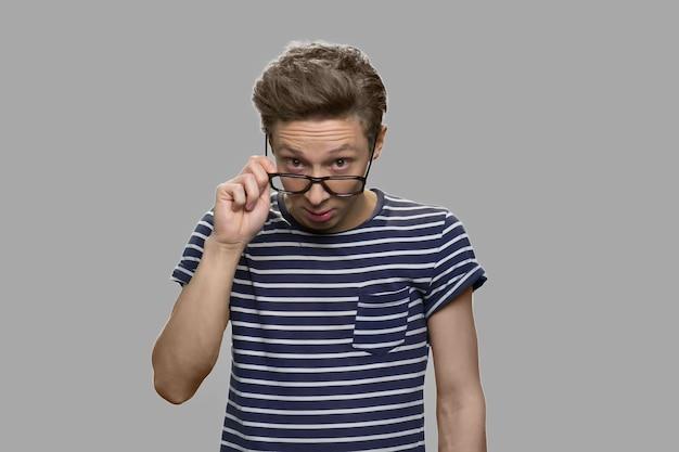 Slimme jongen in bril met een idee. tienerjongen die zijn bril aanpast die peinzende blik heeft. jong grappig genie.