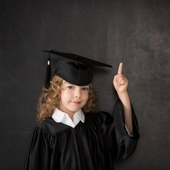Slimme jongen in de klas. gelukkig kind tegen bord. idee concept