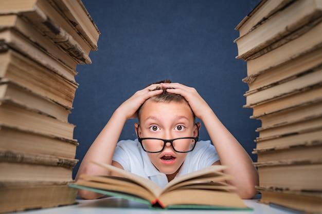 Slimme jongen in glazen gek van het lezen van boek zittend tussen twee stapels boeken