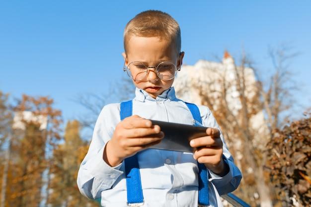 Slimme jongen in glazen met een mobiele telefoon