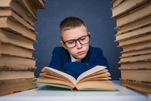 Slimme jongen in glazen zitten tussen twee stapels boeken en boek zorgvuldig lezen
