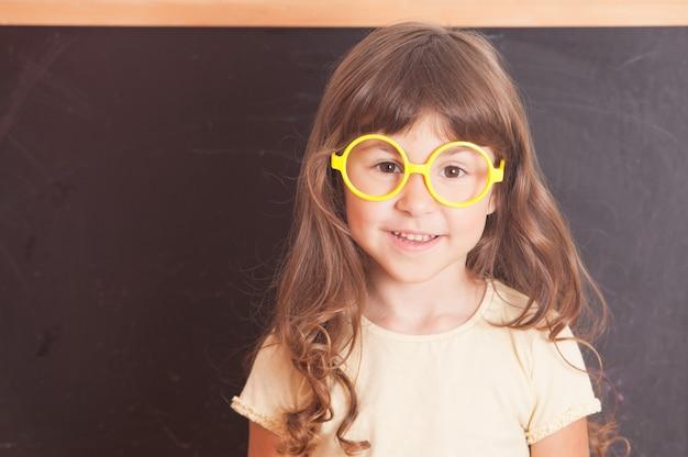 Slimme jongen met een gele bril stond voor een schoolbord