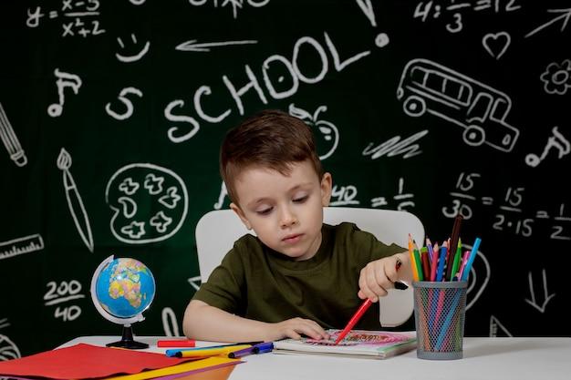 Slimme jongen tekenen aan balie. schooljongen. basisschool student tekenen op de werkplek.