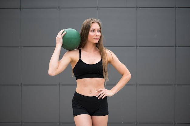 Slimme kijkende vrouw die een bal middelgroot schot houdt