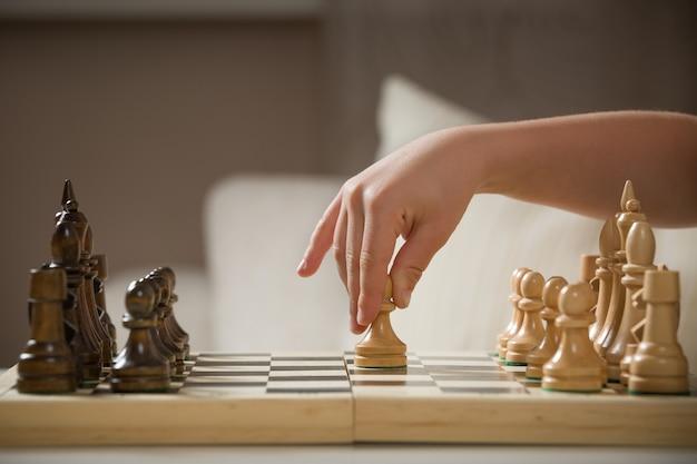 Slimme kinderhand die een schaakfiguur vasthoudt tijdens het schaken thuis