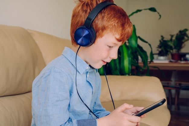 Slimme kleine jongen luisteren naar muziek met mobiele telefoon geluiddichte hoofdtelefoon thuis.