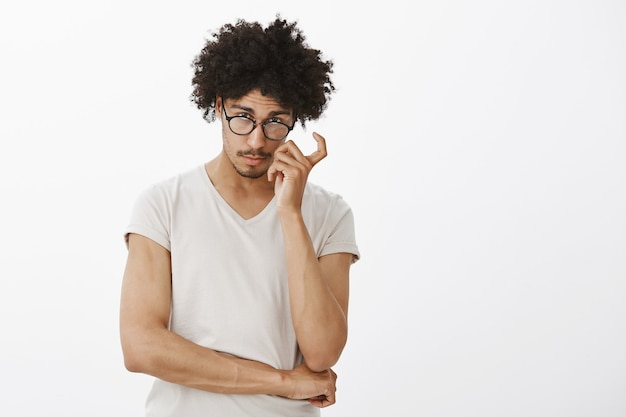 Slimme knappe mannelijke programmeur die nieuwsgierig kijkt, een bril draagt