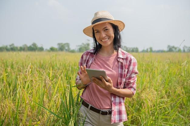 Slimme landbouw met behulp van moderne technologieën in de landbouw. aziatische jonge vrouwelijke agronoom boer met digitale tabletcomputer in rijstveld met behulp van apps en internet, boer zorgt voor haar rijst.