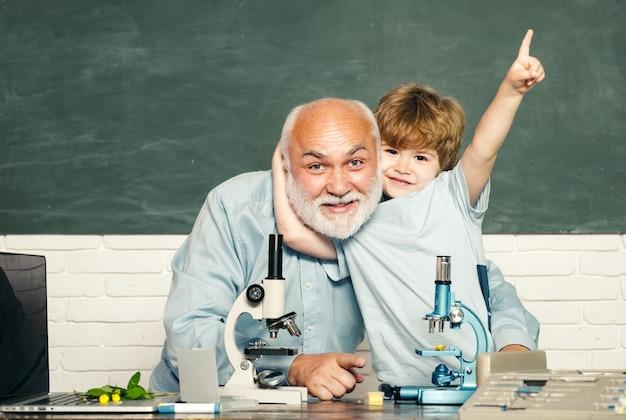 Slimme leerling en oude leraar die op groene muur leren