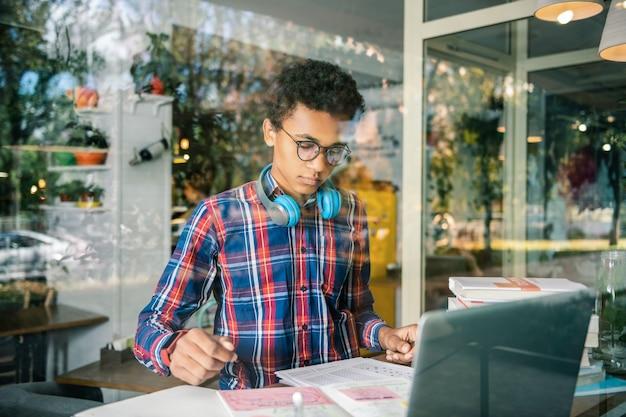 Slimme leerling. ernstige jonge jongen die zijn aantekeningen bekijkt terwijl hij zich op zijn schooltaak concentreert