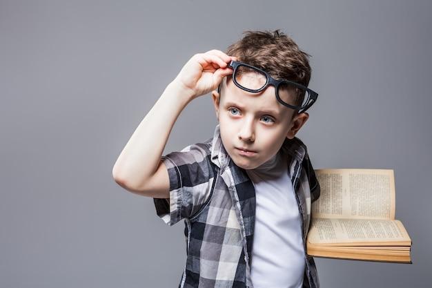 Slimme leerling in glazen met leerboek in handen, studio fotoshoot. kinderopvoeding concept