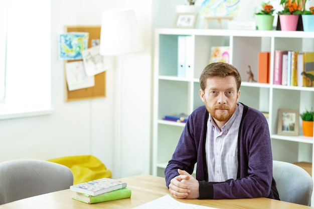 Slimme leraar. kalme bebaarde man zit in een klaslokaal en wacht op zijn studenten terwijl hij een blauw vest draagt