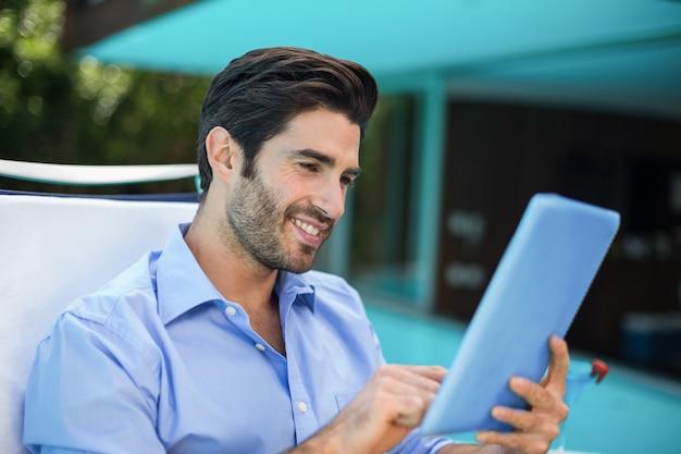 Slimme man met behulp van digitale tablet in de buurt van zwembad
