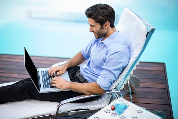Slimme man met laptop in de buurt van zwembad