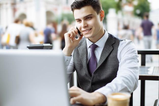 Slimme manager die koffiepauze heeft en op de telefoon in koffie spreekt