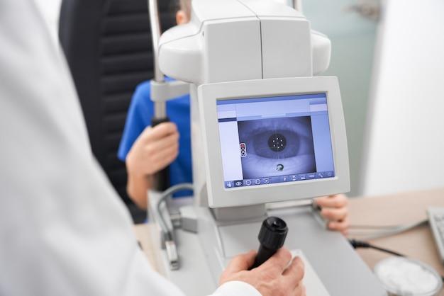 Slimme mannelijke oogarts die machine gebruikt om het gezichtsvermogen te controleren