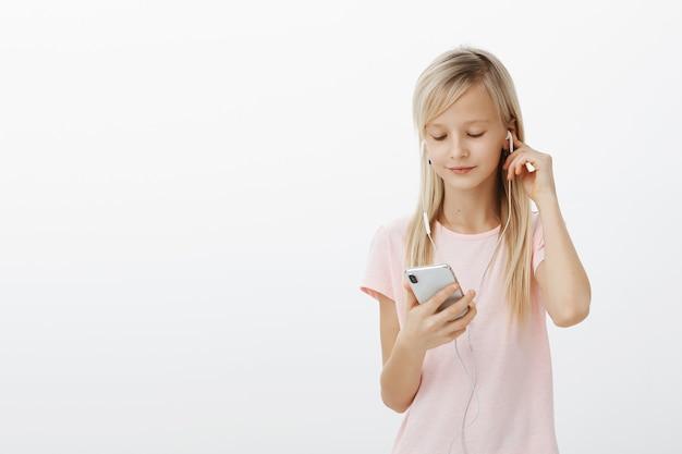 Slimme meid weet alles van gadgets. portret van schattig mooi blond jong kind, oortelefoons dragen en lied plukken in smartphone