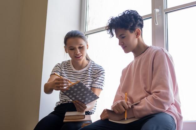 Slimme meid wijst naar pagina van boek en toont haar klasgenoot passage voor leren uit het hoofd tijdens de voorbereiding van huistaak