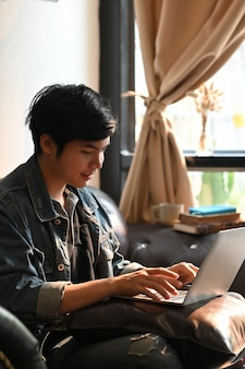 Slimme mens in het overhemd van jean het typen op computerlaptop die het zetten op zijn schoot terwijl het zitten en het ontspannen bij de zwarte leerlaag over comfortabele woonkamervensters en gordijn als achtergrond.