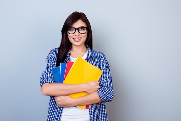 Slimme mooie vrouw in geruit overhemd en bril met voorbeeldenboeken tegen grijze ruimte